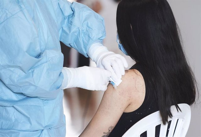 Archivo - Una mujer recibe la vacuna del Covid en Santander