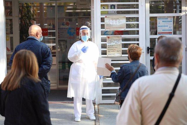 Archivo - Una sanitaria sale a atender a las numerosas personas que hacen cola en el Centro de Salud Vicálvaro-Artilleros en el distrito de Vicálvaro.