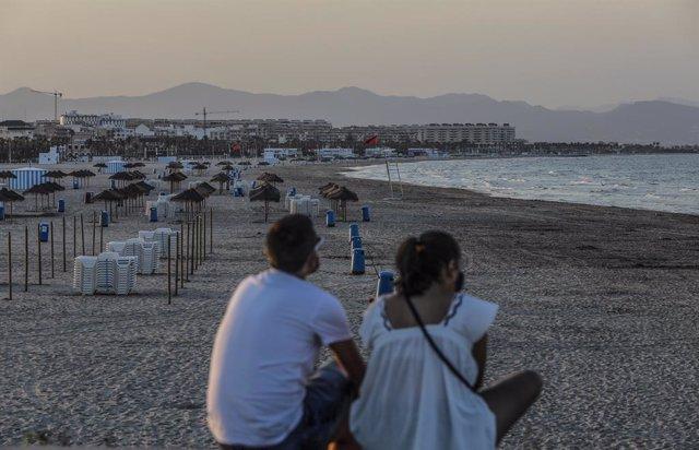 Archivo - Arxiu - Dos joves asseguts contemplen la platja de la Malva-rosa a València