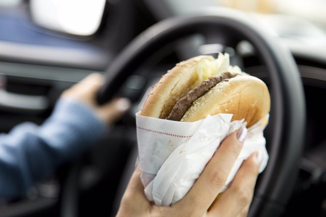 Archivo - Hombre al volante comiendo una hamburguesa.