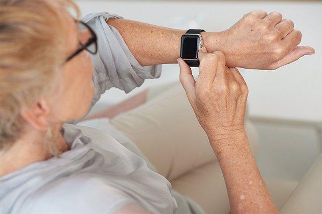 Archivo - Hands of senior woman checking her smartwatch
