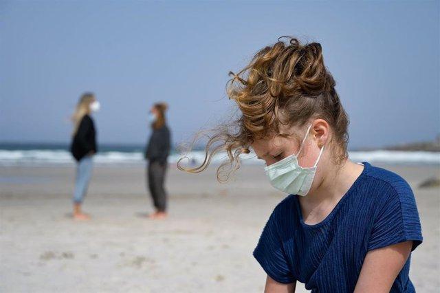 Archivo - Una niña con mascarilla en la playa.