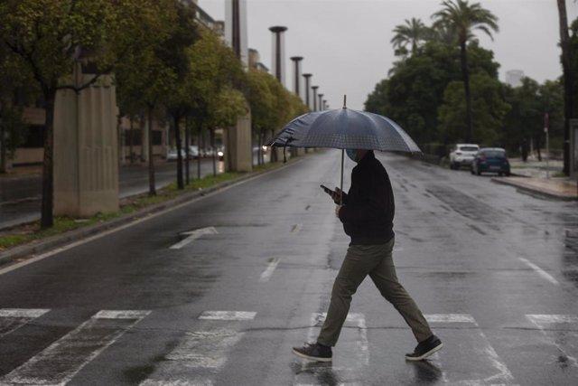 Archivo - Un hombre camina protegido de la lluvia con un paraguas.