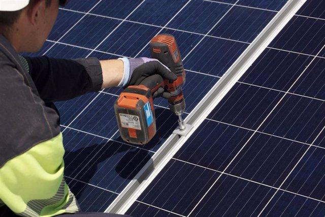 Archivo - Un técnico fija los soportes de una instalación fotovoltaica de autoconsumo de EDP