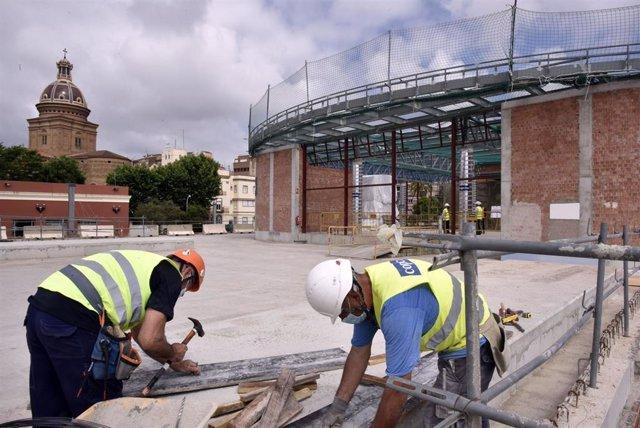 Dos obreros trabajan en las obras de construcción de la nueva estación subterránea de Sant Andreu Comt