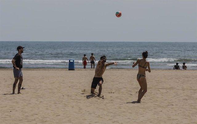 Archivo - Varias personas juegan con una pelota en la Playa de la Malvarrosa, de València (archivo).