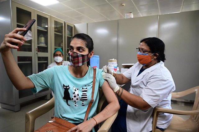 Archivo - 10 May 2021, India, Prayagraj: A girl takes a selfie while a medical worker inoculates Coronavirus (Covid-19) vaccine dose at Moti Lal Nehru Medical college. Photo: Prabhat Kumar Verma/ZUMA Wire/dpa