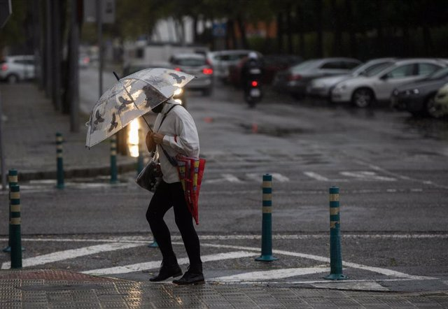 Archivo - Una mujer camina protegida de la lluvia con un paraguas. Las ciudades andaluzas Córdoba, Sevilla, Huelva, Cádiz y Málaga tienen hoy aviso amarillo por acumulaciones de las precipitaciones que podrán llegar a los 25 litros por metro cuadrado en u