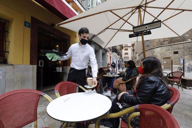 Archivo - Un camarero, con mascarilla, sirve un café en una terraza de Palma.