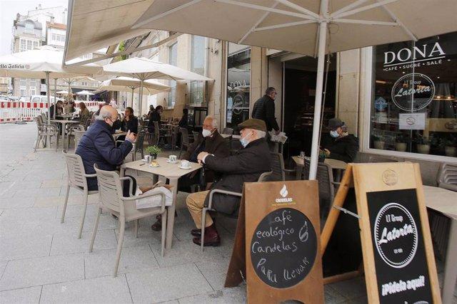 Archivo - Varias personas en una terraza, el día en que entran en vigor nuevas medidas en la hostelería, en Vigo.