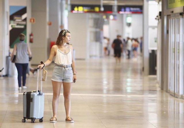 Archivo - Una joven con una maleta en el Aeropuerto Adolfo Suárez Madrid-Barajas durante el verano.