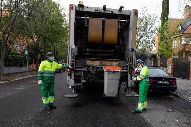Archivo - Dos operarios de recogida de residuos protegidos con mascarilla colocan un cubo de basura