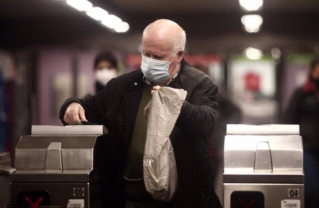 Archivo - Una anciano en los torniquetes del metro de Oporto, Madrid (España), a 17 de noviembre de 2020. Desde la Consejería de  Transportes, Movilidad e Infraestructuras de la Comunidad de Madrid se anunció ayer que a partir del 1 de enero de 2021 se ap