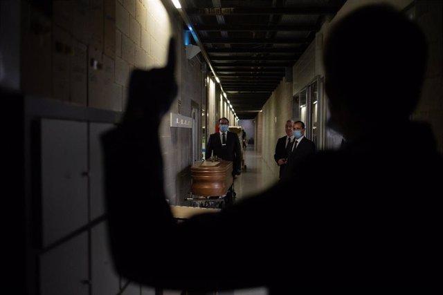 Archivo - Varios operarios del Crematorio de Girona trasladan un ataúd, ya desinfectado, de una víctima con Covid-19, para introducirlo en el horno crematorio, durante el día 53 del estado de alarma por la crisis del coronavirus donde trabajan para dar el