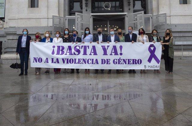 Representantes de los grupos políticos municipales portan una pancarta contra la violencia de género durante el minuto de silencio convocado por el Ayuntamiento de Madrid condenando el asesinato de una vecina de Moratalaz