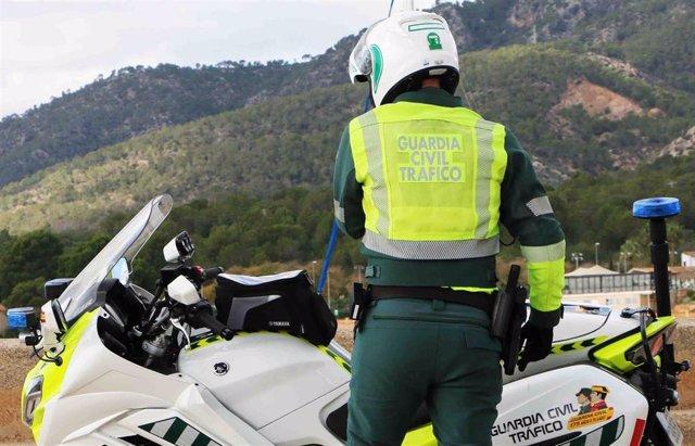 Archivo - Un agente de la Guardia Civil de Tráfico, de espaldas, en una carretera junto a su moto y una montaña al fondo.