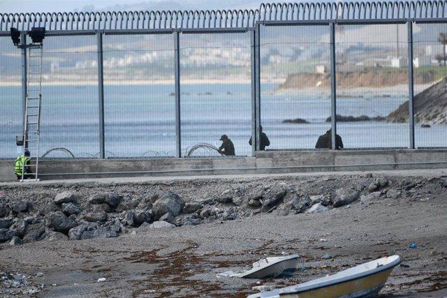 Agentes de la Gendarmería Real marroquí y Fuerzas auxiliares (Mejania) levantan alambradas de concertinas en la parte inferior del vallado en el espigón del Tarajal, a 1 de junio de 2021