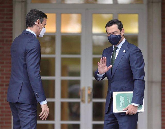 El presidente de la Junta de Andalucía, Juan Manuel Moreno Bonilla (d) saluda a su llegada al Palacio de Moncloa antes de su reunión con el presidente del Gobierno, Pedro Sánchez (i), a 17 de junio de 2021. Se trata de la primera reunión oficial de ambos