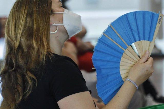 Archivo - Una mujer con mascarilla se abanica, foto de archivo