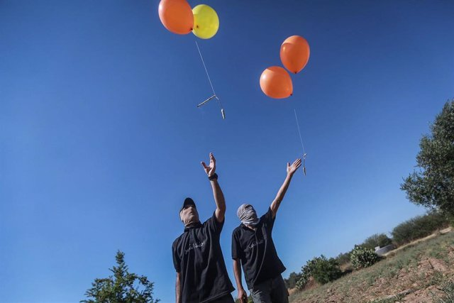 15 June 2021, Palestinian Territories, Gaza City: Masked Palestinians release refrigerant gas-filled balloons, attached to incendiary devices and flammable material, to be propelled by wind into Israeli territory, from an area located to the east of Gaza