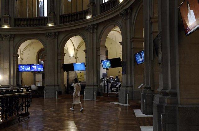Una mujer camina por el interior de la Bolsa de Madrid