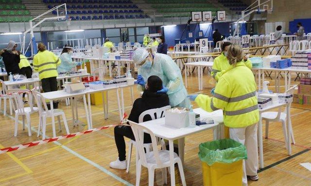 Archivo - Un trabajador sanitario realiza un test de antígenos a un estudiante universitario de la Universidad de Vigo, en Vigo.