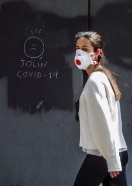 Archivo - Arxiu- Una xica amb mascarilla passa al costat d'una pintada relacionada amb el COVID-19 durant el dia 25 de l'estat d'alarma decretat a conseqüència de la crisi del coronavirus, a València (Comunitat Valenciana, Espanya), a 8 d'abril de 2020.