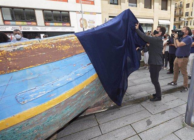 El consejero Santos retira la lona que cubre una patera, protagonista de la exposición para conmemorar el Día Mundial de las Personas Refugiadas