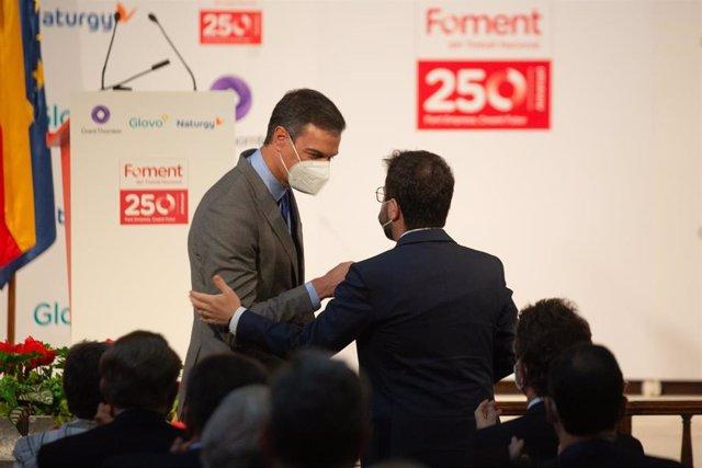 El presidente del Gobierno, Pedro Sánchez (i) y el president de la Generalitat, Pere Aragonés (d), se saludan en un acto el 7 de junio de 2021 en Barcelona
