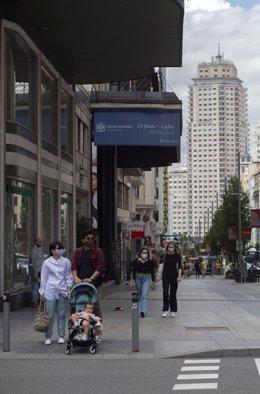 Varias personas caminan por la Gran Vía con mascarilla, a 18 de junio de 2021, en Madrid (España). El presidente del Gobierno, Pedro Sánchez, ha anunciado que las mascarillas dejarán de ser obligatorias en los espacios al aire libre a partir del próximo s