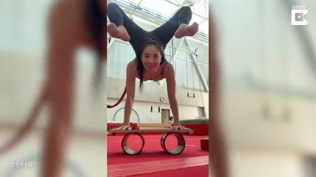 La contorsionista del circo del sol, Baaska Enkhbaatar, hace el pino sobre una tabla apoyada en dos cilindros