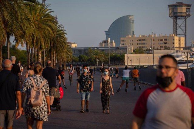 Archivo - Un hombre y una mujer pasean en Barcelona, Catalunya (España), a 28 de julio de 2020. Los rebrotes de las últimas semanas y las restricciones impuestas por países como Reino Unido a los turistas que vienen de España o las recomendaciones de Bélg