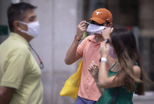 Un hombre se quita la mascarilla, en la Puerta del Sol, a 18 de junio de 2021, en Madrid (España).