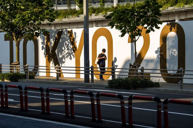 11 June 2021, Japan, Tokyo: A woman walks next to a Tokyo2020 sign at the Olympic Stadium, before the start of the Tokyo 2020 Olympic Games. The Summer Olympics are taking place from 23 July to 8 August 2021. Photo: Rob Walbers/BELGA/dpa