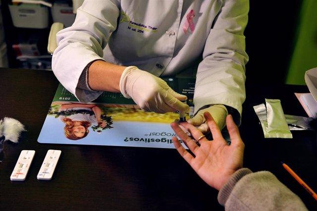 Archivo - Una farmacéutica de la Farmacia Portal Martínez Soto toma una muestra de sangre para realizar un test de cribado del coronavirus en Barbadás, Ourense, Galicia (España), a 19 de octubre de 2020. Las farmacias ourensanas que colaboran con la Conse