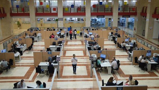 Empleados atienden a contribuyentes de manera presencial desde una oficina de la Agencia Tributaria.