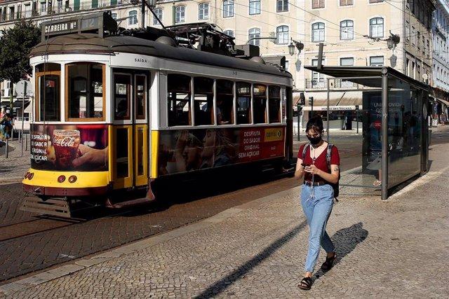 Archivo - Una mujer con mascarilla junto a un tranvía en Lisboa