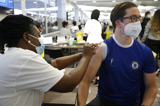 Un ciutadà amb la samarreta del Chelsea FC rep una dosi de la vacuna Pfizer en les jornades de vacunació en estadis de futbol londinencs