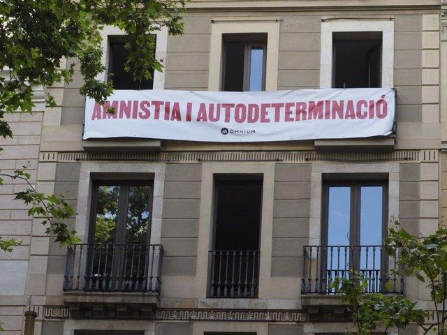 Òmnium desplega una pancarta davant el Liceu per demanar a Sánchez amnistia i autodeterminació
