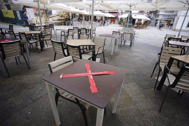 Archivo - Una mesa de una terraza tachada con una cinta de prohibición en una calle de Vigo,