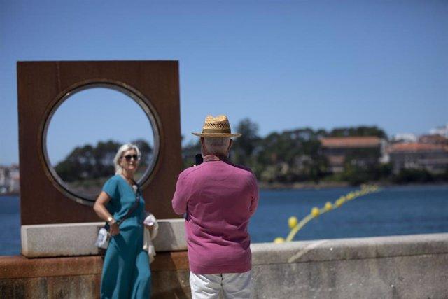 Un hombre echa una foto a una mujer en el paseo marítimo de la playa de Sanxenxo, a 4 de junio de 2021, en Sanxenxo, Pontevedra, Galicia, (España). El aumento de las temperaturas y la progresiva mejora de la situación epidemiológica ha colaborado en que l