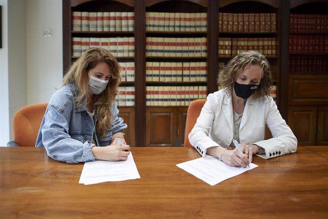 La gerente de AJE, Adriana Eransus, y la directora general Izaskun Goñi firman el convenio.