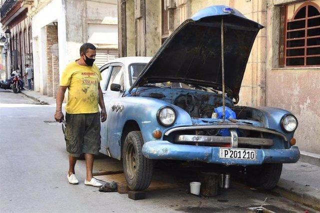 Un hombre con mascarilla arregla un coche en La Habana