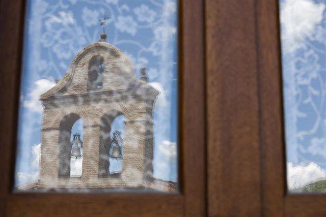 Reflejo de una iglesia en un cristal de una vivienda.
