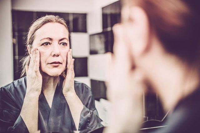 Archivo - Mujer madura mirándose en el espejo.