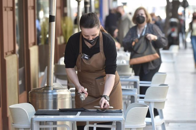 Archivo - Una camarera preparando las mesas de una terraza