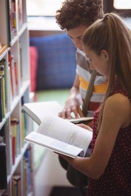 Archivo - Estudiantes leyendo un libro.