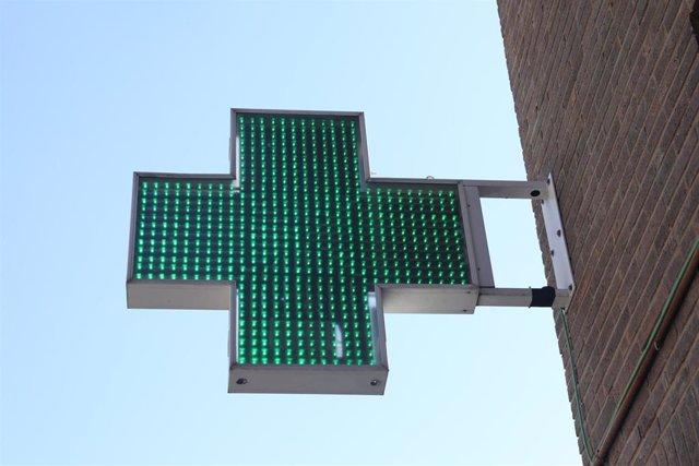 Archivo - Icono verde encendido de una farmacia en una calle de Madrid.