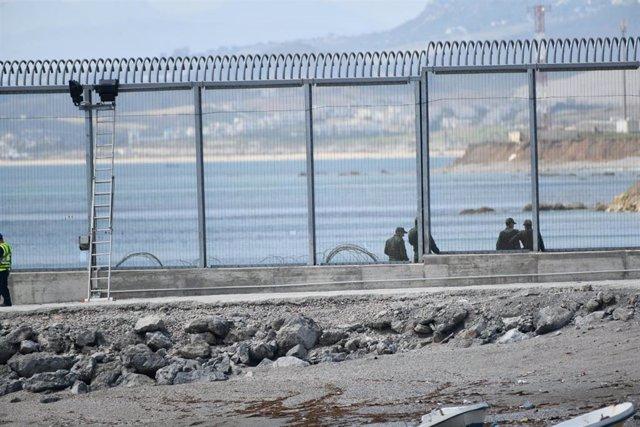 Agentes de la Gendarmería Real marroquí y Fuerzas auxiliares (Mejania) levantan alambradas de concertinas en la parte inferior del vallado en el espigón del Tarajal, a 1 de junio de 2021, en Marruecos.