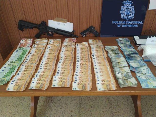 Archivo - El dinero y las armas decomisadas en los registros.